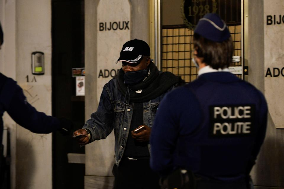 Police officers check the documents of a man while patrolling in central Brussels during a curfew imposed by the Belgian government (REUTERS)