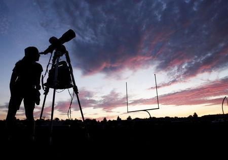 A woman looks through a telescope on the football field at Madras High School the evening before a solar eclipse in Madras, Oregon, U.S., August 20, 2017. Picture taken August 20, 2017. REUTERS/Jason Redmond