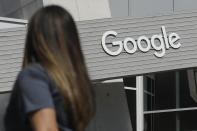 FILE - In this Sept. 24, 2019, file photo a woman walks below a Google sign on the campus in Mountain View, Calif. Five technology giants reported mixed earnings results Thursday, Oct. 29, 2020 a sign of varying fortunes as they try to rebound from an pandemic-related economic slowdown earlier this year. While all five — Amazon, Google parent Alphabet, Facebook, Apple and Twitter — exceeded analyst expectations, gloomy forecasts and other uncertainties led to share-price declines for all but Alphabet in after-market trading. (AP Photo/Jeff Chiu, File)