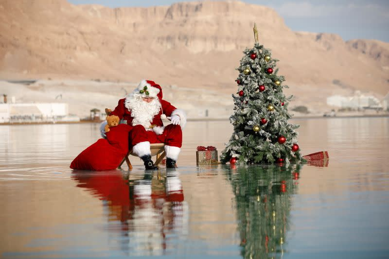 Issa Kassissieh, wearing a Santa Claus costume, looks on as he poses for a picture while sitting next to a Christmas tree on a salt formation in the Dead Sea, near Ein Bokeq