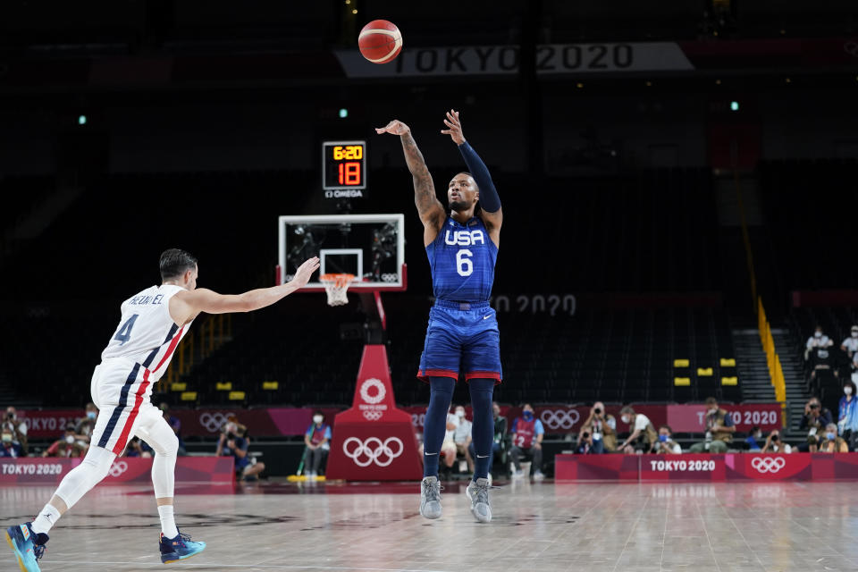United States' Damian Lillard (6) shoots a 3-point basket over France's Thomas Heurtel, left, during a men's basketball preliminary round game at the 2020 Summer Olympics, Sunday, July 25, 2021, in Saitama, Japan. (AP Photo/Charlie Neibergall)