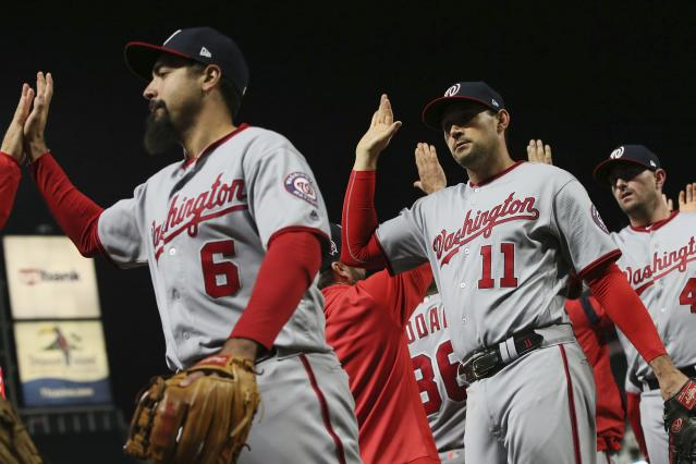 Washington Nationals' Anthony Rendon, left, and Ryan Zimmerman go through the celebration line after the Nationals defeated the Minnesota Twins 6-2 in a baseball game Wednesday, Sept. 11, 2019, in Minneapolis. Zimmerman had three RBIs. (AP Photo/Jim Mone)