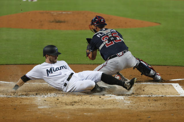 Miami Marlins' Jon Berti, left,slides in safe to score on a single by Starlin Castro as Atlanta Braves catcher Tyler Flowers (25) waits for the throw during the first inning of a baseball game, Sunday, Aug. 11, 2019, in Miami. (AP Photo/Wilfredo Lee)