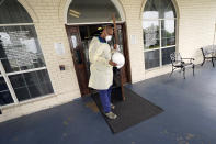Dr. Robin Armstrong holds open the door to The Resort at Texas City nursing home, where he is the medical director, Tuesday, April 7, 2020, in Texas City, Texas. Armstrong is treating nearly 30 residents of the nursing home with the anti-malaria drug hydroxychloroquine, which is unproven against COVID-19 even as President Donald Trump heavily promotes it as a possible treatment. Armstrong said Trump's championing of the drug is giving doctors more access to try it on coronavirus patients. More than 80 residents and workers have tested positive for coronavirus at the nursing home. (AP Photo/David J. Phillip)