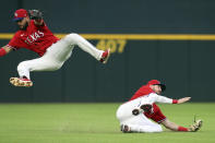 Texas Rangers shortstop Isiah Kiner-Falefa leaps to avoid left fielder David Dahl (21) as he catches a fly ball hit by Seattle Mariners' Kyle Seager during the third inning of a baseball game Friday, May 7, 2021, in Arlington, Texas. (AP Photo/Richard W. Rodriguez)