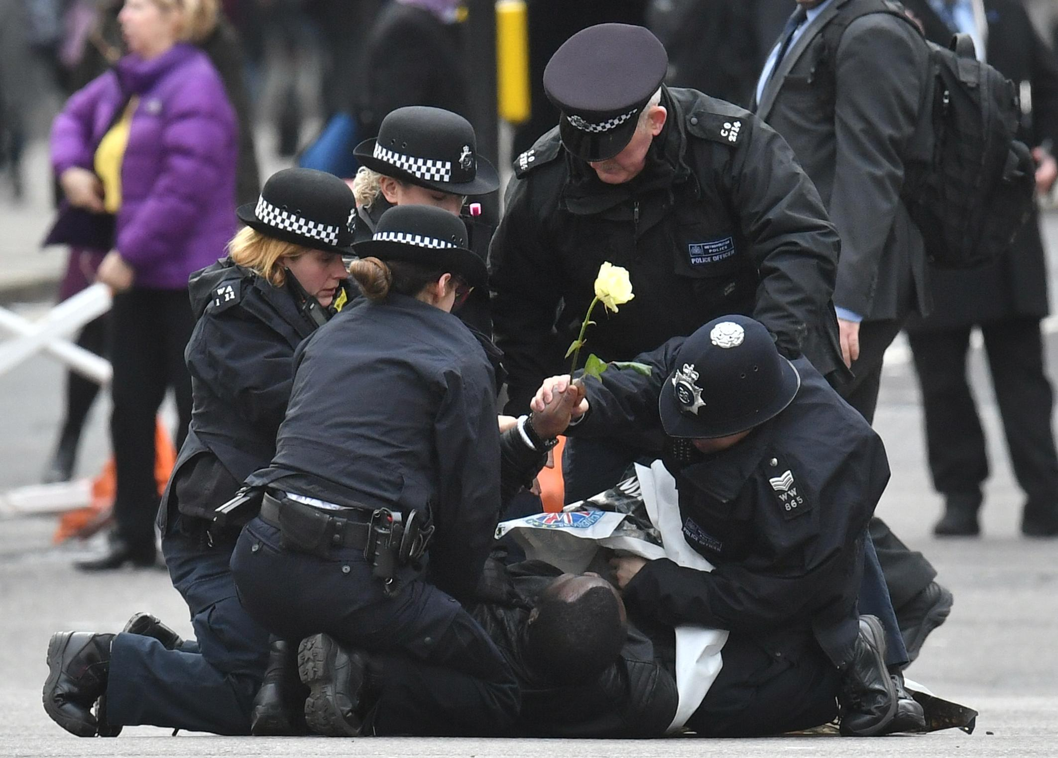 Police officers detain one of two men who ran into the road outside Westminster Abbey, London, ahead of the Commonwealth Service.