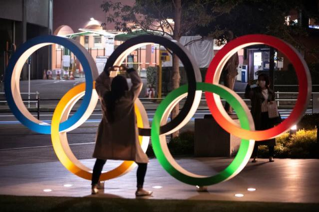 Women wearing protective face masks, following the outbreak of the coronavirus, take a picture next to The Olympic rings in front of the Japan Olympics Museum in Tokyo