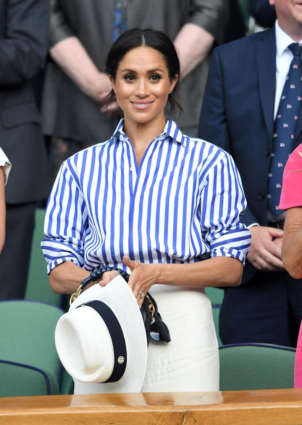 <p>The Duchess of Sussex wore a chic blue and white striped button-down at the famed Wimbledon Tennis Championships. She paired the look with an elegant white fedora. </p>