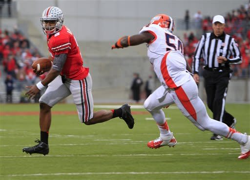 Ohio State quarterback Braxton Miller, left, runs past Illinois defender Justin Staples to score a touchdown during the third quarter of an NCAA college football game Saturday, Nov. 3, 2012, in Columbus, Ohio. Ohio State won 52-22. (AP Photo/Jay LaPrete)