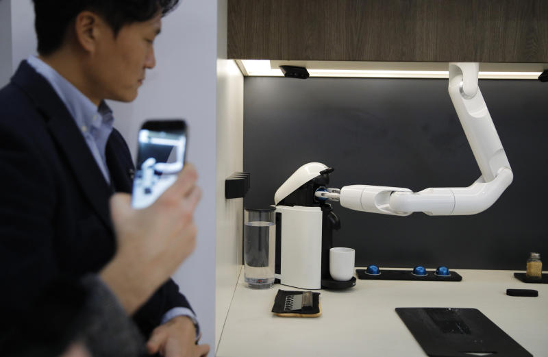 People watch as the Bot Chef makes coffee during a demonstration at the Samsung booth during the CES tech show, Tuesday, Jan. 7, 2020, in Las Vegas. The robot is designed to help with cooking tasks, not to make a meal all on it's own. (AP Photo/John Locher)