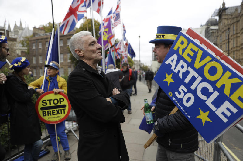 A Brexit supporter, center, speaks to Anti-Brexit remain in the European Union supporter Steve Bray, right, as he protests opposite the Houses of Parliament in London, Thursday, Oct. 17, 2019. EU Brexit negotiator Michel Barnier says that British Prime Minister Boris Johnson told the EU he is confident he can get a deal through the House of Commons.  (AP Photo/Matt Dunham)