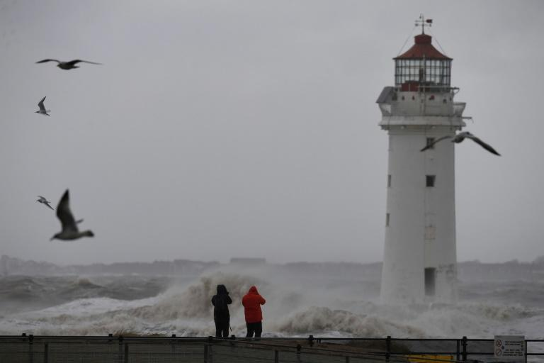 People take photographs of the waves in a stormy sea near the lighthouse in New Brighton, northwest England, on January 3, 2018, as Storm Eleanor swept over the country