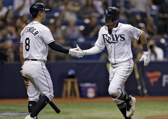 Tampa Bay Rays' Willy Adames, right, celebrates with Rob Refsnyder (8) after Adames scored on a single by Mallex Smith off Toronto Blue Jays relief pitcher Joe Biagini during the sixth inning of a baseball game Tuesday, June 12, 2018, in St. Petersburg, Fla. (AP Photo/Chris O'Meara)