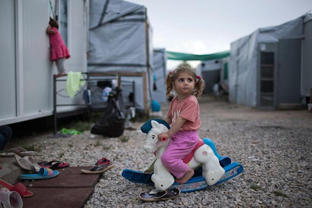 <p>Three-year-old Ragika from Syria plays with a toy horse at the refugee camp of Ritsona about 86 kilometers (53 miles) north of Athens, Greece, May 25, 2017. (Photo: Petros Giannakouris/AP) </p>