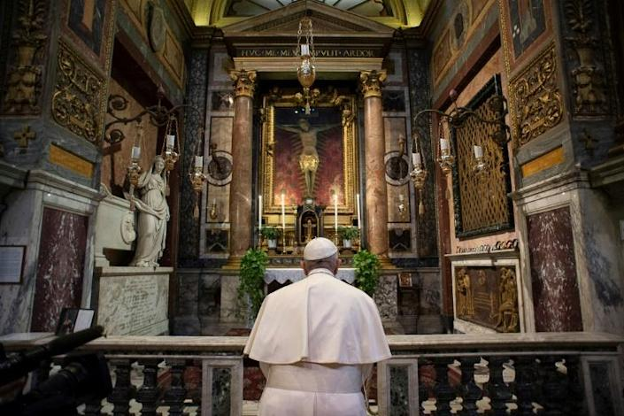 The 83-year-old pontiff's unannounced visit to a church with a crucifix from the times of the Great Plague came with Italy's hospitals running out beds (AFP Photo/-)