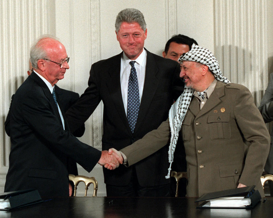 """FILE - President Bill Clinton, center, looks on as Israeli Prime Minister Yitzhak Rabin, left, and PLO leader Yasser Arafat shake hands in the East Room of the White House after signing the Mideast accord in Washington on Sept. 28, 1995. The documentary """"The Human Factor"""" shows the behind-the-scenes story of the U.S.'s effort to secure peace in the Middle East. (AP Photo/Doug Mills, File)"""