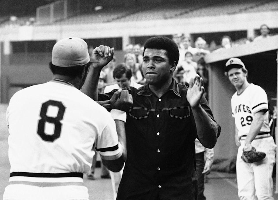 Muhammad Ali clowns with Willie Stargell on a baseball field.