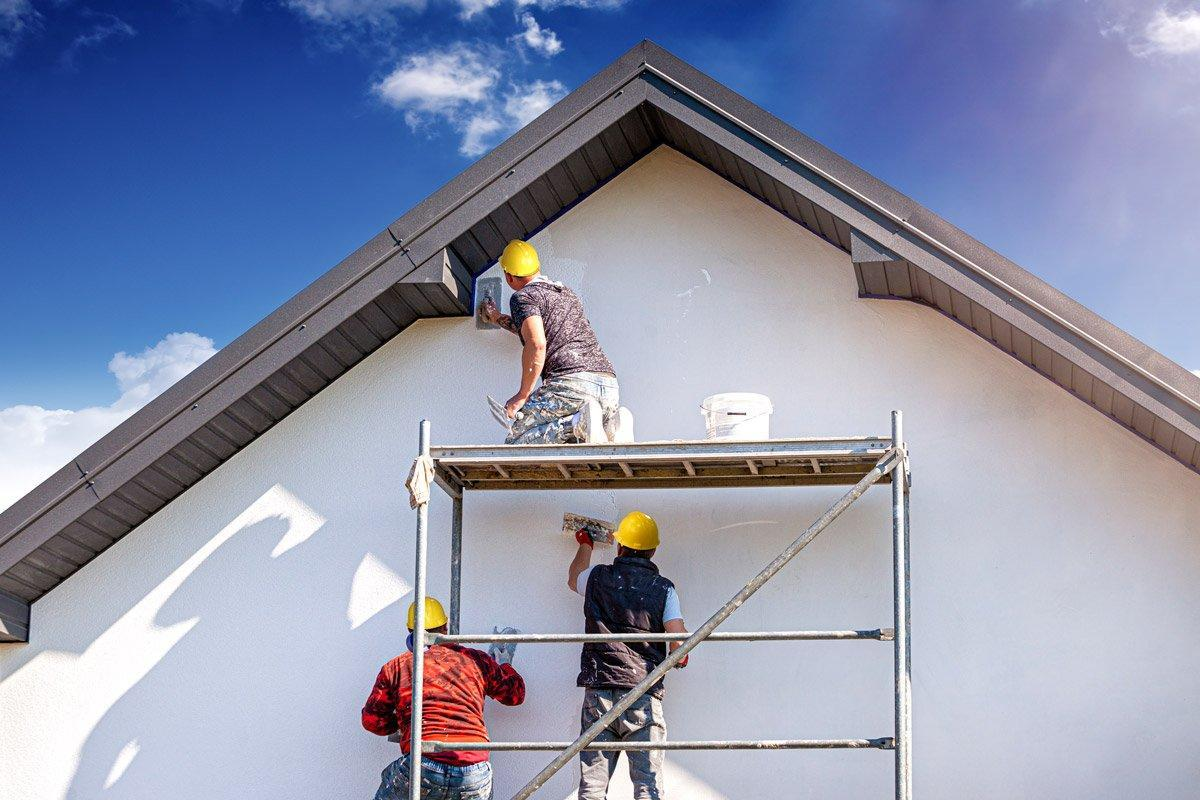 People work on the exterior of a house.