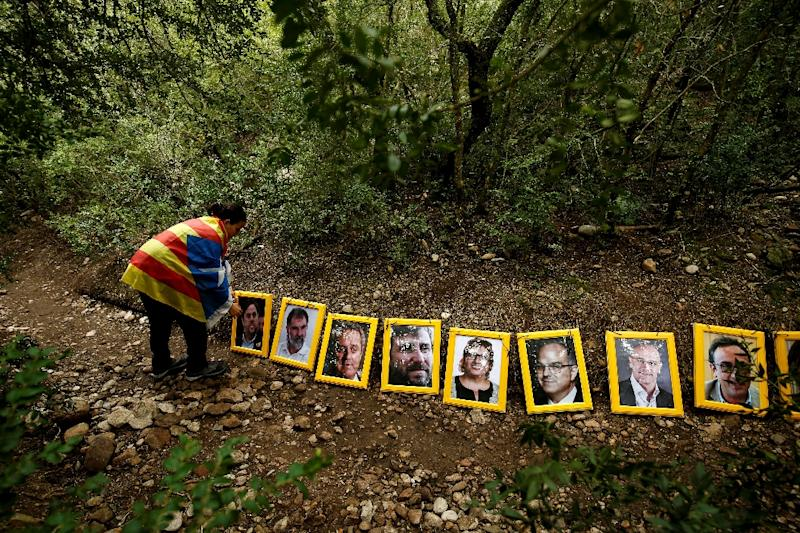 A protester puts a portrait of Catalonia's jailed vice president Oriol Junqueras next to portraits of other jailed and self-exiled members of Catalonia's ousted government (AFP Photo/PAU BARRENA)