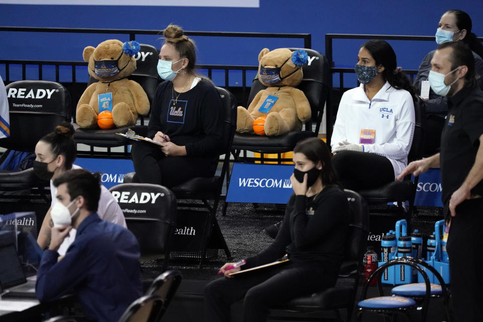 Teddy bears are seated on the UCLA bench during the first half of an NCAA college basketball game against Stanford, Monday, Dec. 21, 2020, in Los Angeles. (AP Photo/Marcio Jose Sanchez)