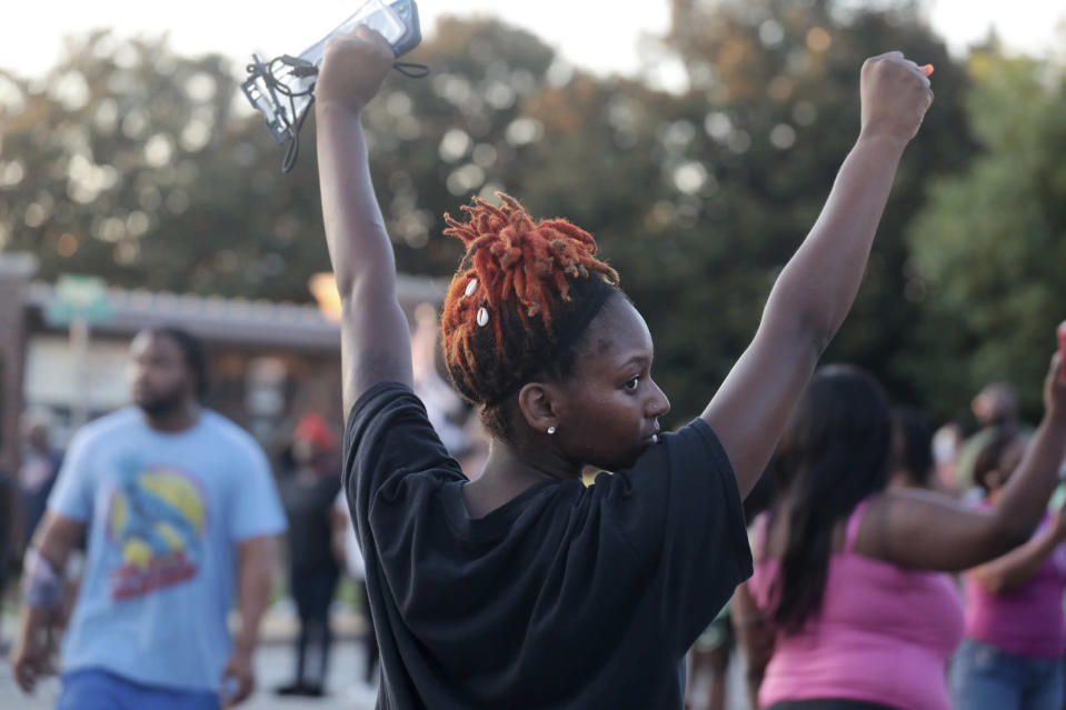 A protester raises her arms Wednesday, June 23, 2021 in downtown Rock Hill, S.C. Demonstrators converged outside a South Carolina police station for a second day Thursday, protesting the arrest of two men by officers in Rock Hill who were recorded on a Facebook video wrestling and throwing punches with the two. (Tracy Kimball/The Charlotte Observer via AP)
