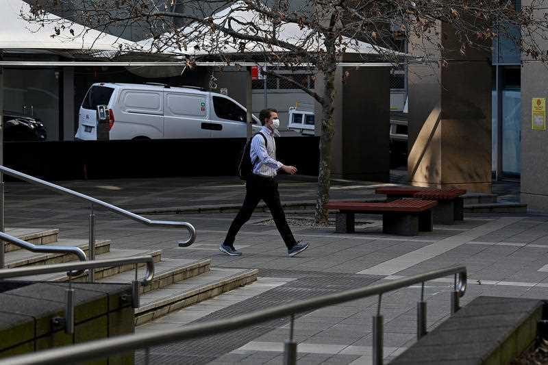 A man wearing a face mask walks through an empty plaza in the central business district of North Sydney.