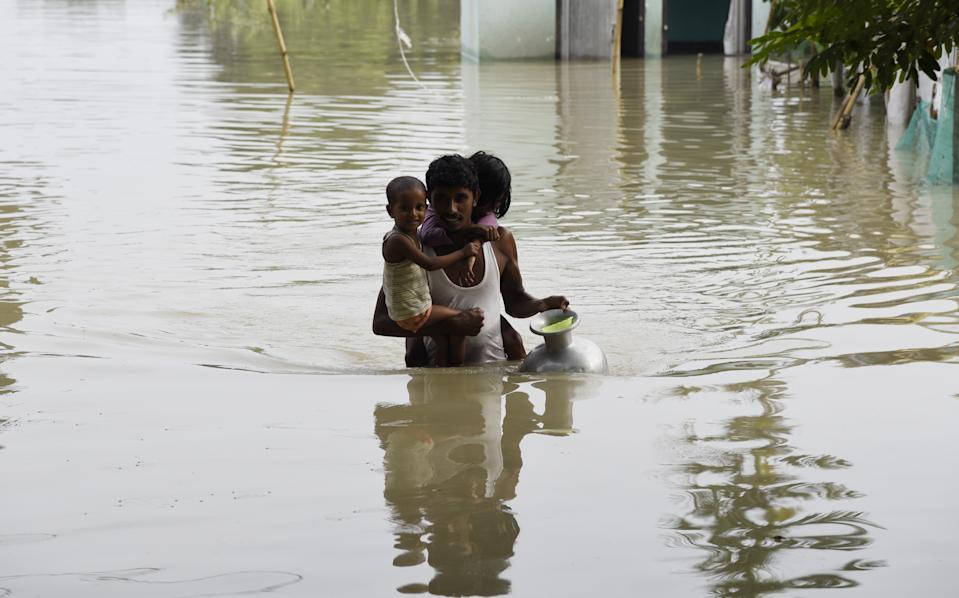 A man carries his children to a safer place in a flood-affected village of Kamrup district of Assam, India, on July 14, 2020. Villages in Assam were flooded due to heavy rains. The rising water level inundated houses, residents were forced to move to a safer place. (Photo by Hafiz Ahmed/Anadolu Agency via Getty Images)