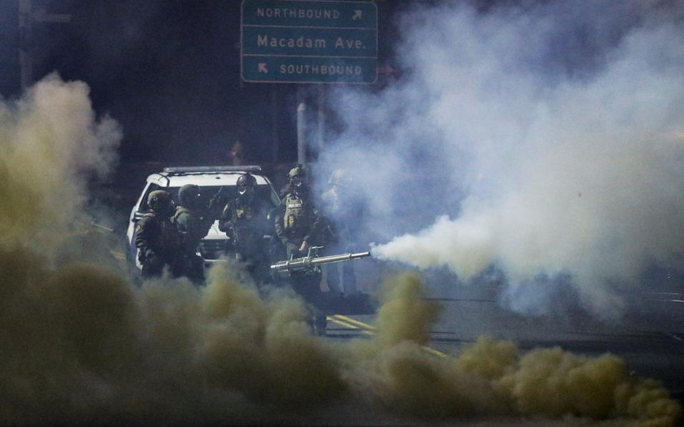 Gas-masked police using a large device to pump clouds of tear gas - Lindsey Wasson/Reuters