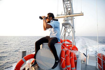 A member of the Libyan Coast Guard uses a pair of binoculars as he searches for migrants off the coast of Tripoli, Libya, August 9, 2017. REUTERS/Hani Amara