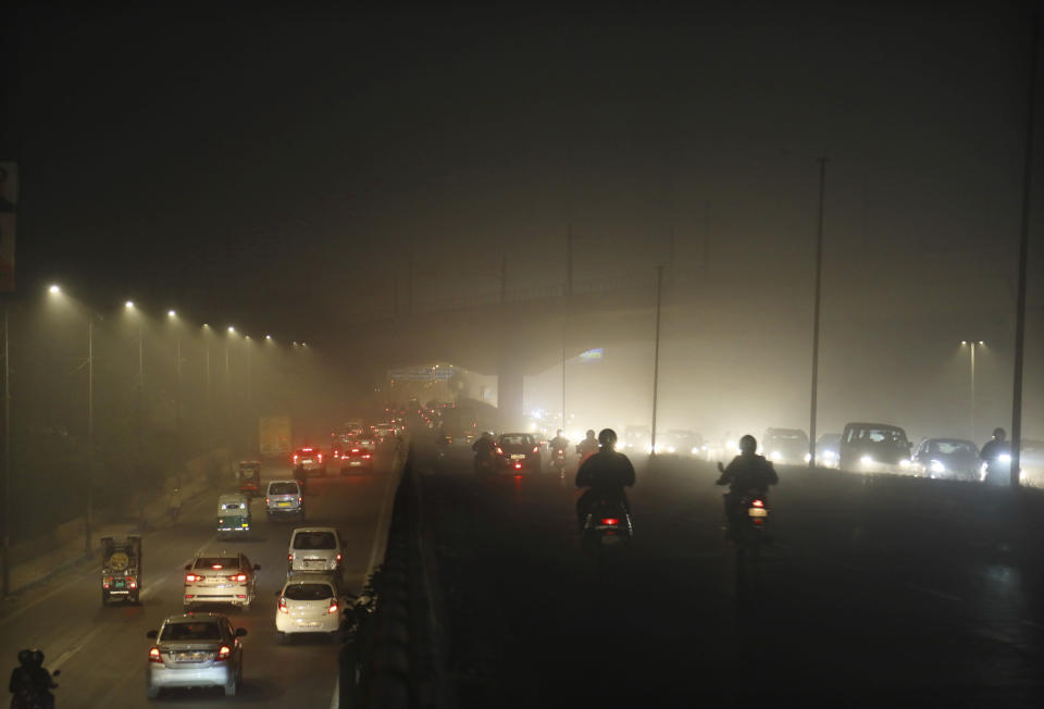 Commuters drive on a road engulfed in thick smog in New Delhi, India, Thursday, Nov. 5, 2020. A thick quilt of smog lingered over the Indian capital and its suburbs on Friday, fed by smoke from raging agricultural fires that health experts worry could worsen the city's fight against the coronavirus. Air pollution in parts of New Delhi have climbed to levels around nine times what the World Health Organization considers safe, turning grey winter skies into a putrid yellow and shrouding national monuments. (AP Photo/Manish Swarup)