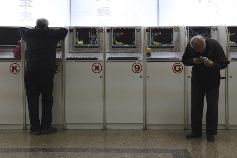 Chinese men monitor stock prices at a brokerage in Beijing, Friday, Oct. 19, 2018. Asian stock markets sank Friday after Wall Street declined on losses for tech and industrial stocks and Chinese economic growth slowed. (AP Photo/Ng Han Guan)