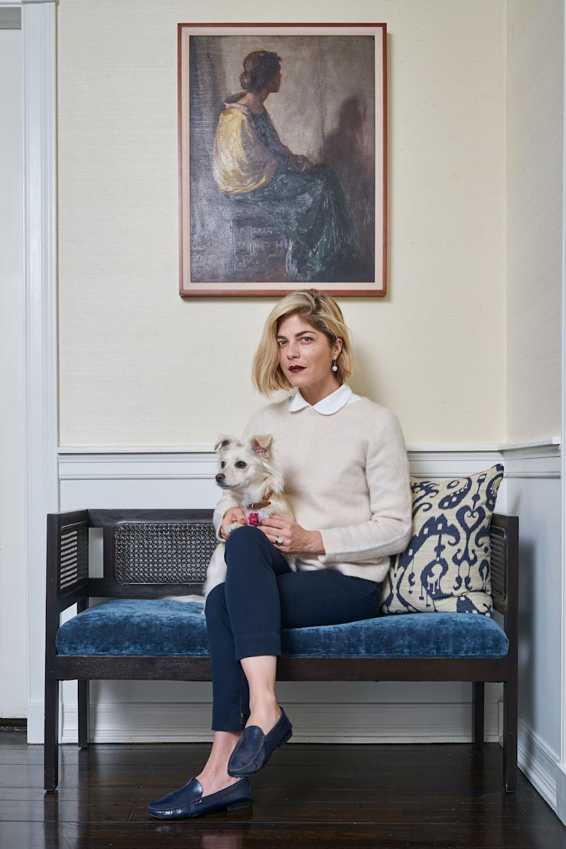 Blair and her pup, Pippa, relax in the in a corner of the living room. Interior designer Bryan Wark gave new life to an antique cane bench with a cobalt velvet cushion. Then he topped it with an ikat pillow he made.