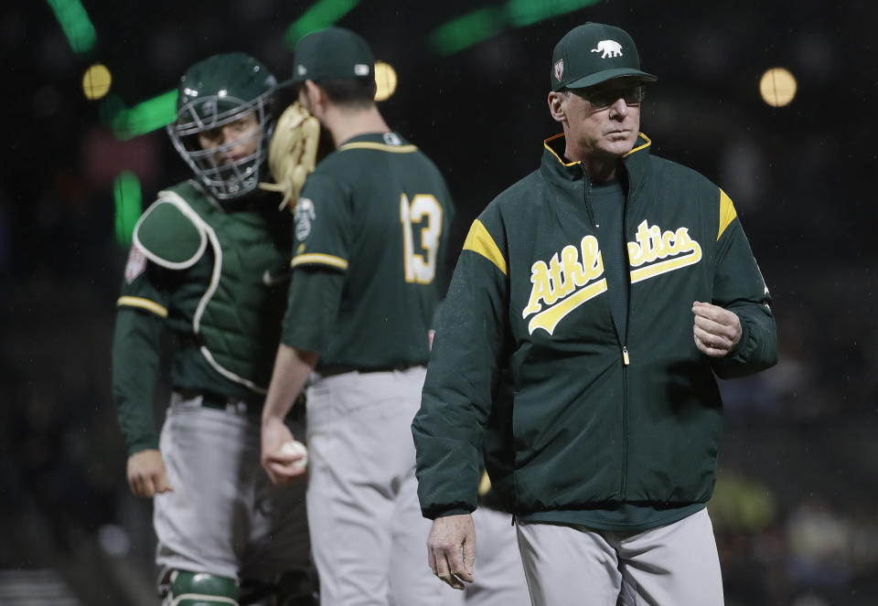 Oakland Athletics manager Bob Melvin, right, walks toward the dugout after changing pitchers during the sixth inning of an exhibition baseball game against the San Francisco Giants in San Francisco, Tuesday, March 26, 2019. (AP Photo/Jeff Chiu)