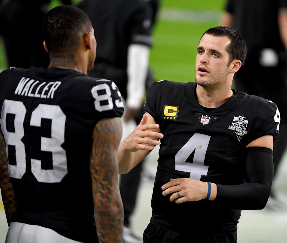 LAS VEGAS, NEVADA - DECEMBER 26:  Quarterback Derek Carr #4 of the Las Vegas Raiders talks with tight end Darren Waller #83 on the sideline in the first half of their game against the Miami Dolphins at Allegiant Stadium on December 26, 2020 in Las Vegas, Nevada. The Dolphins defeated the Raiders 26-25.  (Photo by Ethan Miller/Getty Images)