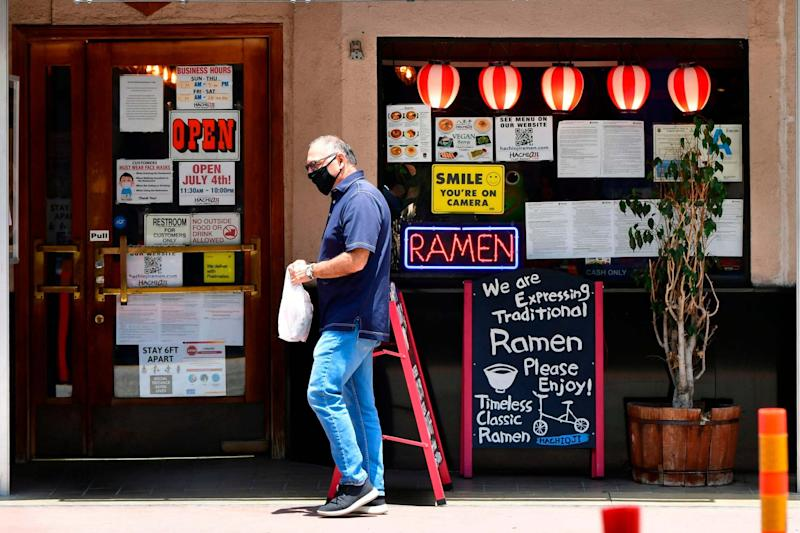 A man wearing a facemask walks past a Ramen restaurant in Los Angeles (AFP via Getty Images)
