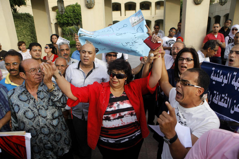Enas Abdel-Dayem, head of the Cairo Opera House, center, is greeted by employees and activists as they chant anti-Muslim Brotherhood slogans during a protest demanding the resignation of Egyptian culture minister at the opera house garden in Cairo, Egypt, Thursday, May 30, 2013. The Cairo Opera House has become a new battleground between supporters and opponents of Egypt's Islamist president, this time fighting over the direction of the Middle East s oldest music institution. The new culture minister fired the opera s head in what he calls a campaign to bring in new blood across the artistic scene. But her staff refuse any new boss and have closed the curtain on all performances, accusing the minister of bending to Islamist pressure. (AP Photo/Amr Nabil)