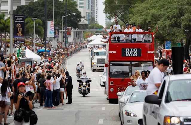 MIAMI, FL - JUNE 25: Fans cheer as the Miami Heat pass by in a victory parade through the streets during a celebration for the 2012 NBA Champion Miami Heat on June 25, 2012 in Miami, Florida. The Heat beat the Oklahoma Thunder to win the NBA title. (Photo by Joe Raedle/Getty Images)