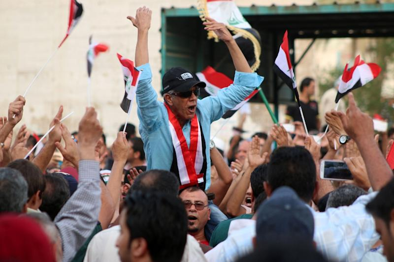 An Iraqi man chants slogans as other wave national flags during a demonstration against corruption and poor services in Baghdad on August 7, 2015 (AFP Photo/Haider Mohammed Ali)