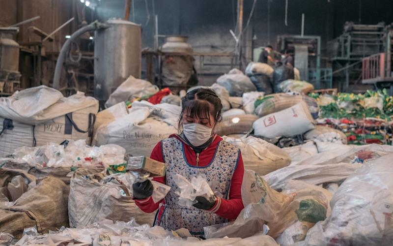 A worker wearing a protective mask sorts plastic at the United Plastic Bag Recyclers (Ruboplast) manufacturing facility in Ecatepec, Mexico State, Mexico - Bloomberg