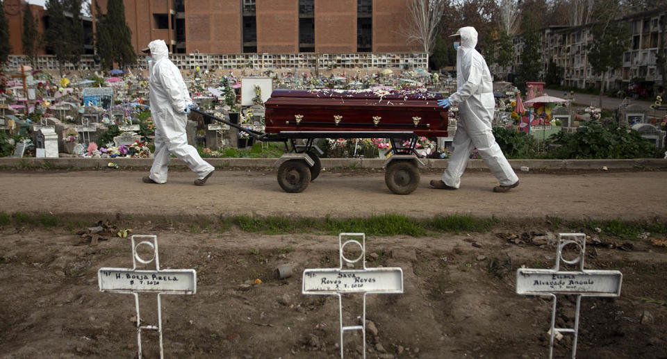 TOPSHOT - Gravedigger Fernando Quezada (R), 27, and a co-worker carry a coffin at the General Cemetery in Santiago, on August 5, 2020, amid the COVID-19 novel coronavirus pandemic. - Used to dealing with death, COVID-19 has put gravediggers to test as they have never before faced such a physical and emotional situation, with burials giving them no rest. (Photo by Claudio REYES / AFP) (Photo by CLAUDIO REYES/AFP via Getty Images)