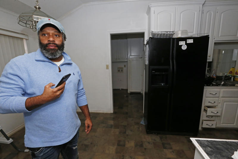 Marcus Morris inspects his girlfriend's house in Jackson, Miss., as Pearl River flood water covers the floor, Sunday, Feb. 16, 2020. Residents of Jackson braced for the possibility of catastrophic flooding in and around the Mississippi capital as the Pearl River rose precipitously after days of torrential rain. (AP Photo/Rogelio V. Solis)