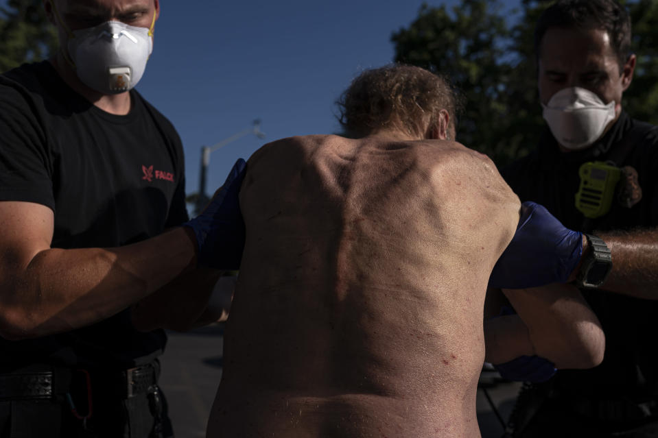 Cody Miller, right, with the Salem Fire Department, along with Falck Northwest ambulance personnel, treats a man experiencing heat exposure at a cooling center during a heat wave, Saturday, June 26, 2021, in Salem, Ore. (AP Photo/Nathan Howard)