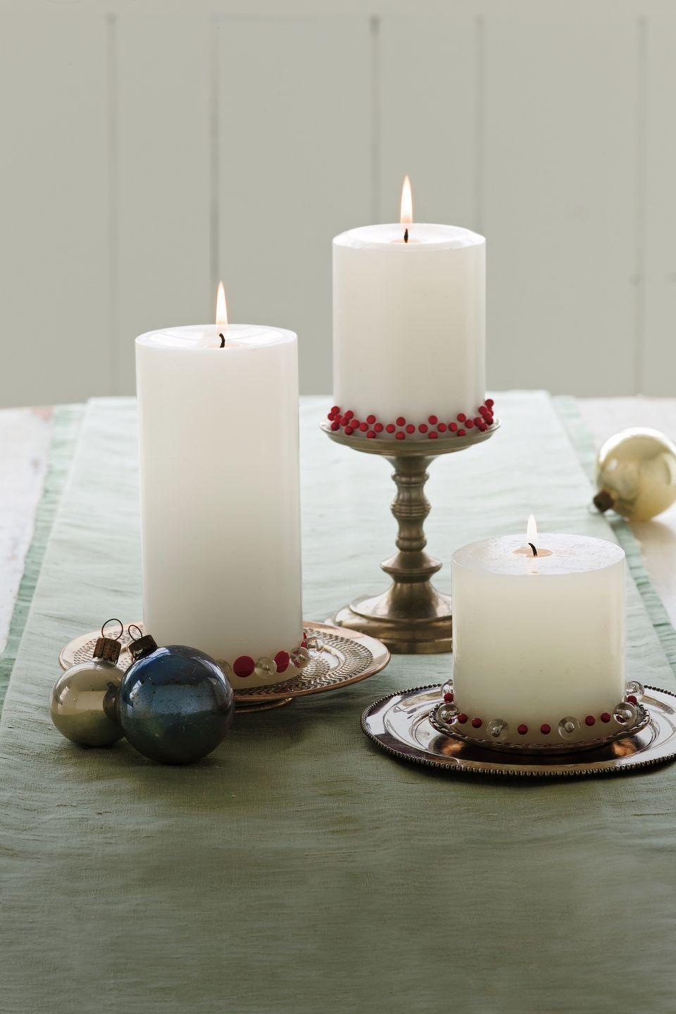 <p>Decorative candles are rarely cheap, and when they've burned down, your investment has burned up. For a more affordable glow, buy plain pillar candles and embellish them with thumbtacks and pushpins. </p>