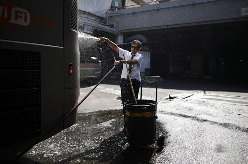 A driver cleans a bus at the Central Bus Station on May 29. (Photo: Corinna Kern/Reuters)