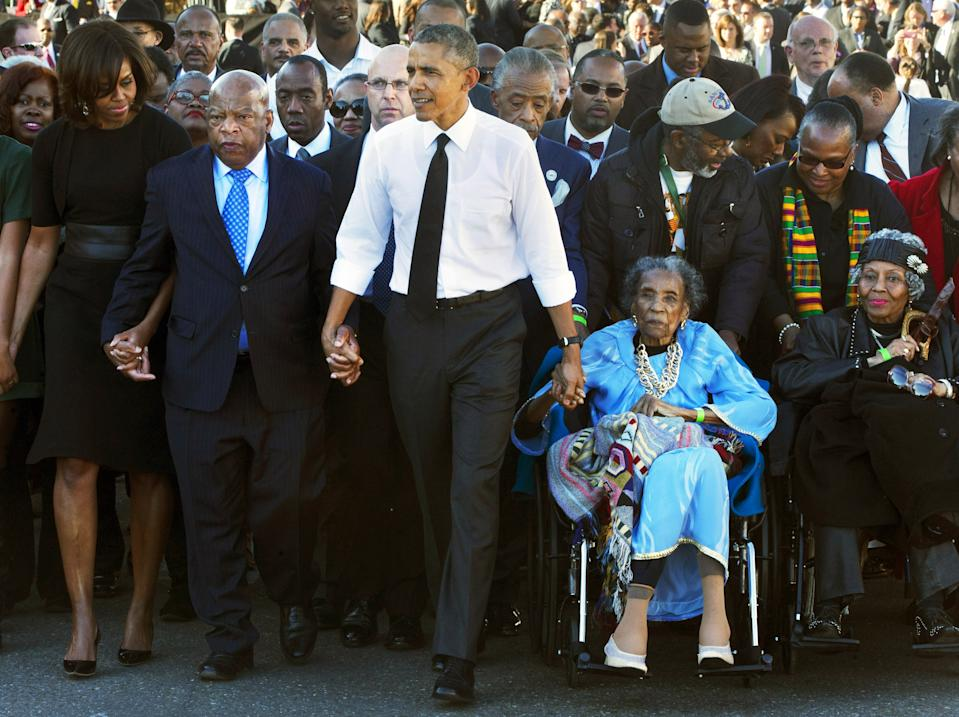 """President Barack Obama, center, holds hands with Rep. John Lewis, D-Ga., left, and Amelia Boynton Robinson, right, who were both beaten during """"Bloody Sunday,"""" as they walk across the Edmund Pettus Bridge in Selma, Ala., for the 50th anniversary of """"Bloody Sunday"""" on March 7, 2015.  (Photo: Jacquelyn Martin/AP)"""