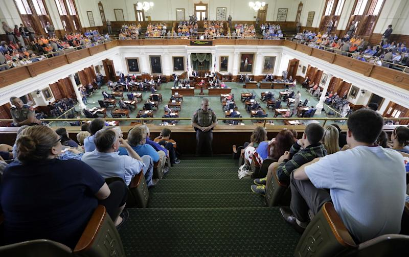 Texas state troopers keep watch as supporters and opponents of an abortion bill, mostly dressed in blue and orange to show their side, sit in the gallery of the Texas Senate chambers as lawmakers debate before the final vote, Friday, July 12, 2013, in Austin, Texas. The bill would require doctors to have admitting privileges at nearby hospitals, only allow abortions in surgical centers, dictate when abortion pills are taken and ban abortions after 20 weeks. (AP Photo/Eric Gay)