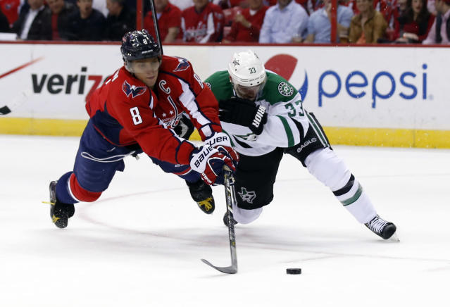 Washington Capitals right wing Alex Ovechkin (8), from Russia, tries to shoot as he is guarded by Dallas Stars defenseman Alex Goligoski (33) in the first period of an NHL hockey game, Tuesday, April 1, 2014, in Washington. (AP Photo/Alex Brandon)