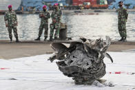 Indonesian marines look at a large part of a plane recovered from the waters off Java Island where Sriwijaya Air flight SJ-182 crashed on Saturday, at Tanjung Priok Port in Jakarta, Indonesia, Monday, Jan. 11, 2021. The search for the black boxes of the crashed Sriwijaya Air jet intensified Monday to boost the investigation into what caused the plane carrying 62 people to nosedive at high velocity into the Java Sea. (AP Photo/Tatan Syuflana)