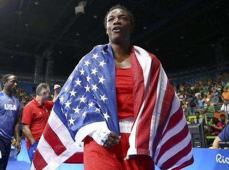 2016 Rio Olympics - Boxing - Final - Women's Middle (75kg) Final Bout 270 - Riocentro - Pavilion 6 - Rio de Janeiro, Brazil - 21/08/2016. Claressa Shields (USA) of USA wears her national flag as she celebrates after winning her bout. REUTERS/Peter Cziborra