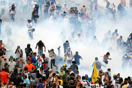 Demonstrators are seen amidst tear gas fired by police during an opposition rally in Caracas, Venezuela, April 6, 2017. REUTERS/Christian Veron